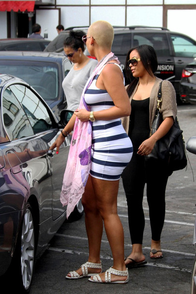 Amber Rose Amber Rose accentuates her curvy figure in a tight fitting striped dress as she and her friends visits The Hair Shop in Hollywood, which specializes in wigs an hair extensions.