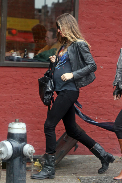 Model and expectant mother Gisele Bundchen tries to stay dry while out in the West Village with a friend.