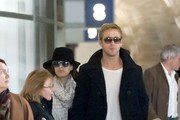 Eva Mendes and Ryan Gosling hold hands as they make their way through Charles de Gaulle Airport with their luggage.