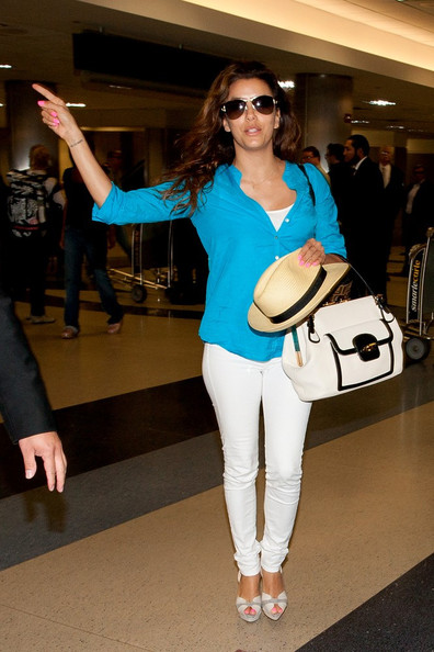 Eva Longoria arrives at LAX (Los Angeles International Airport) wearing a bright blue shirt.