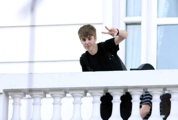Justin Bieber Justin Bieber flashes the peace sign to fans from the balcony of the Copacabana Hotel.