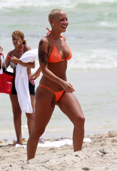 Rapper Kanye West and girlfriend Amber Rose enjoy some time in the sun in Miami Beach. Amber opts to wear a skimpy bikini with a G-string bottom, and at one point goes topless. Kanye doesn't seem amused by the attention they receive and flips off the cameras.