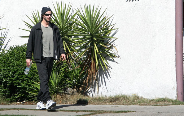 Keanu Reeves parks his Porsche Carrera and finds a shady area to do some shadowboxing exercises.