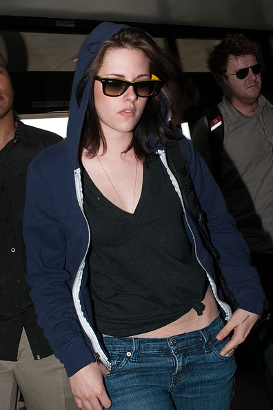 Kristen Stewart departs with bodyguards at Los Angeles International Airport (LAX). She has to pass through the metal detector several times.