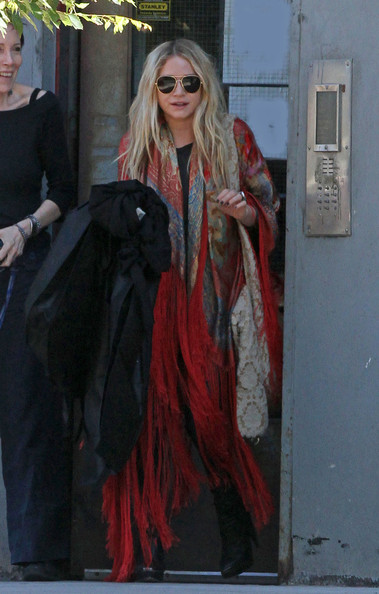 Mary-Kate Olsen Mary-Kate Olsen tries to hide behind her coat as she leaves her apartment carrying a dress bag.