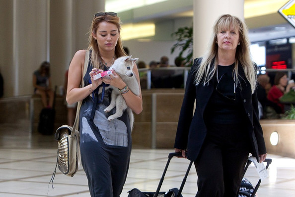 Miley Cyrus Miley Cyrus prepares to depart LAX (Los Angeles International Airport) with her puppy.