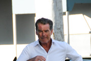 Pierce Brosnan with a scar over his right eye crosses the road
