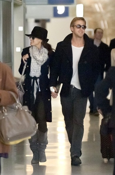 Ryan Gosling Eva Mendes and Ryan Gosling hold hands as they make their way through Charles de Gaulle Airport with their luggage.