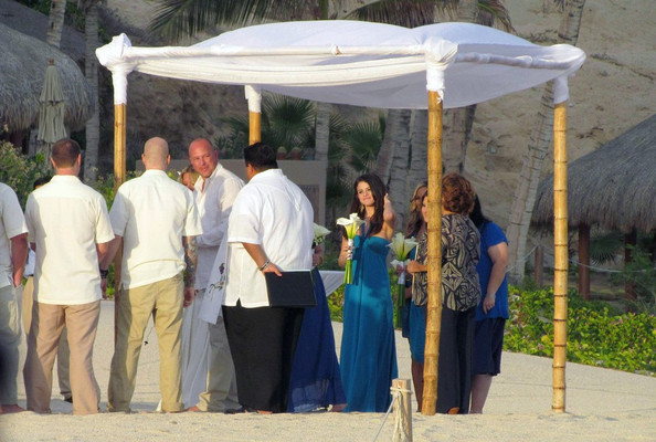 Selena Gomez Selena Gomez acts as a bridesmaid for her friend Shannon Larossi's beach side wedding ceremony. Whilst off duty she cuddles up to boyfriend Justin Bieber .NON- EXCLUSIVE December 08, 2011.