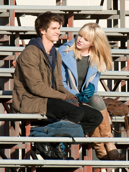 Andrew Garfield and Emma Stone film scenes for the upcoming Spider-Man movie.  Garfield plays Peter Parker / Spider-Man and Stone plays Gwen Stacy, Peter Parker's first love.  The scene takes place on high school bleachers at a football field.  Parker hands Stacy a vial and they kiss.