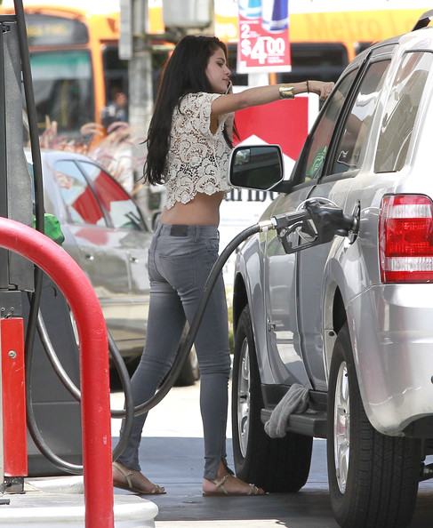 """Wizards of Waverly Place"" star Selena Gomez chats away on her cell phone as she pumps gas and washes her windshield at a 76 station in Encino, California on May 26, 2012. Selena, you're not supposed to use your cell phone at gas stations! That's dangerous!"