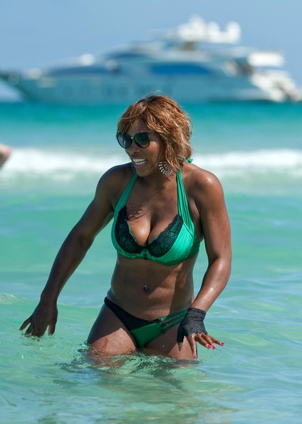 Serena Williams took her fashionable self to the beach today in Miami. Wearing a green bikini and a single lace glove, Serena sat with her friends on loungers drinking cocktails before taking to the ocean to play a pickup game of football. It was boys verses girls as the two teams battled the waves, laughed out loud and playfully splashed each other. Of course it was Serena who came out on top, but then she does have a heavy advantage being the sports star that she is. Serena's love of fashion was clear in her choice of bikini and madonna style lace glove, and her nails freshly painted, courtesy of herself!