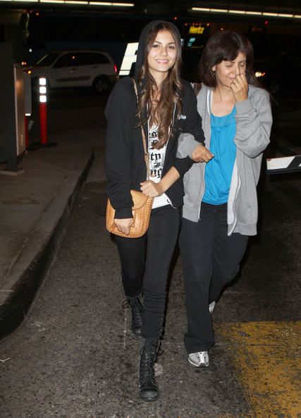 Victoria Justice Actress Victoria Justice arrives at LAX airport with her mother wearing a Upright Citizens Brigade hoodie.