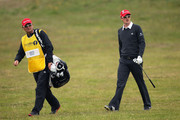Justin Rose of England walks with his caddy Mark Fulcher during the first round of The 140th Open Championship at Royal St George's on July 14, 2011 in Sandwich, England.