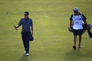Justin Rose of England walks up the 18th fairway with his caddie Mark Fulcher during the first round of The 143rd Open Championship at Royal Liverpool on July 17, 2014 in Hoylake, England.