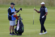 Tiger Woods of the United States hands a club to caddie Joe LaCava during a practice round prior to the 148th Open Championship held on the Dunluce Links at Royal Portrush Golf Club on July 16, 2019 in Portrush, United Kingdom.