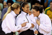 (L-R) Irene van Dyk, Maria Tutaia and Anna Scarlett of New Zealand celebrate prior to receiving their gold medals during the medal ceremony for Women Finals Gold medal match between Australia and New Zealand at the Thyagaraj Sports Complex during day eleven of the Delhi 2010 Commonwealth Games on October 14, 2010 in Delhi, India.