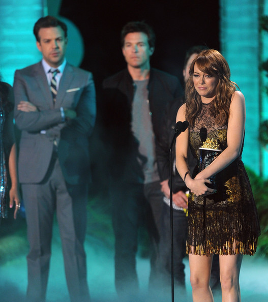 Actres Emma Stone accepts the Best Comedic Performance award from actors Jason Sudeikis and Jason Bateman onstage during the 2011 MTV Movie Awards at Universal Studios' Gibson Amphitheatre on June 5, 2011 in Universal City, California.