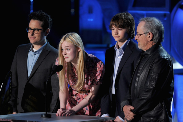 (L-R) Producer J.J. Abrams, actors Elle Fanning, Joel Courtney, and producer Steven Spielberg speak onstage during the 2011 MTV Movie Awards at Universal Studios' Gibson Amphitheatre on June 5, 2011 in Universal City, California.