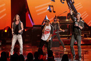 Rapper Nelly (C) performs with singers Tyler Hubbard (L) and Brian Kelley (R) of Florida Georgia Line onstage during the 2013 American Music Awards at Nokia Theatre L.A. Live on November 24, 2013 in Los Angeles, California.