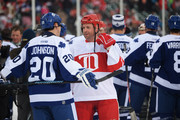 Mike Johnson #20 of the Toronto Maple Leafs talks with Aaron Ward #27 of the Detroit Red Wings following the end of the first game of the 2013 Hockeytown Winter Festival Alumni Showdown on December 31, 2013 at Comerica Park in Detroit, Michigan.