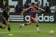 Thomas Muller #25 of Bayern Munich brings the ball up the pitch on Sean Franklin #7 the MLS All-Stars during the second half of the game at Providence Park on August 6, 2014 in Portland, Oregon.
