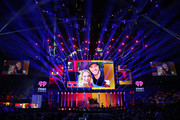 (EDITORIAL USE ONLY. NO COMMERCIAL USE) A selfie photo of co-host Candace Cameron Bure and Luke Bryan is projected on screens while hosts Bobby Bones (L) and Candace Cameron Bure speak onstage during the 2018 iHeartCountry Festival By AT&T at The Frank Erwin Center on May 5, 2018 in Austin, Texas.