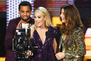 Carrie Underwood (C) accepts the Favorite Album - Country award for 'Cry Pretty' and Favorite Female Artist - Country award from Michael Ealy (L) and Cobie Smulders (R) onstage during the 2019 American Music Awards at Microsoft Theater on November 24, 2019 in Los Angeles, California.