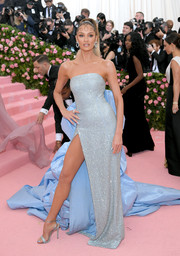 Candice Swanepoel flaunted her shoulders and leg in a high-slit strapless gown with a voluminous ruffle train at the 2019 Met Gala.