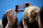A spectatot takes a photo in the Men's Semifinal match between Roger Federer of Switzerland and Novak Djokovic of Serbia on day eleven of the 2020 Australian Open at Melbourne Park on January 30, 2020 in Melbourne, Australia.