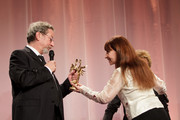 Director Robert Guediguian (L) is awarded 'Swann d'Or' Best Director by his wife/actress Ariane Ascaride (R) during 26th Cabourg Romantic Film Festival on June 16, 2012 in Cabourg, France.