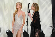 Frida Aasen (L) models charity items while Sharon Stone speaks onstage at the 28th Annual Elton John AIDS Foundation Academy Awards Viewing Party sponsored by IMDb, Neuro Drinks and Walmart on February 09, 2020 in West Hollywood, California.