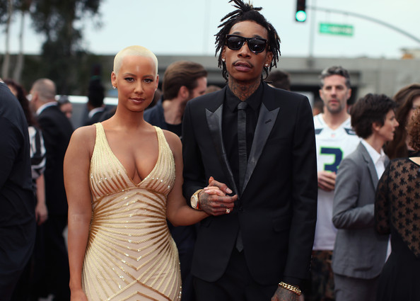 Recording artist Wiz Khalifa (R) featured wearing Converse in support of the GRAMMY Foundation's GRAMMY Camp and model Amber Rose attend the 56th GRAMMY Awards at Staples Center on January 26, 2014 in Los Angeles, California.