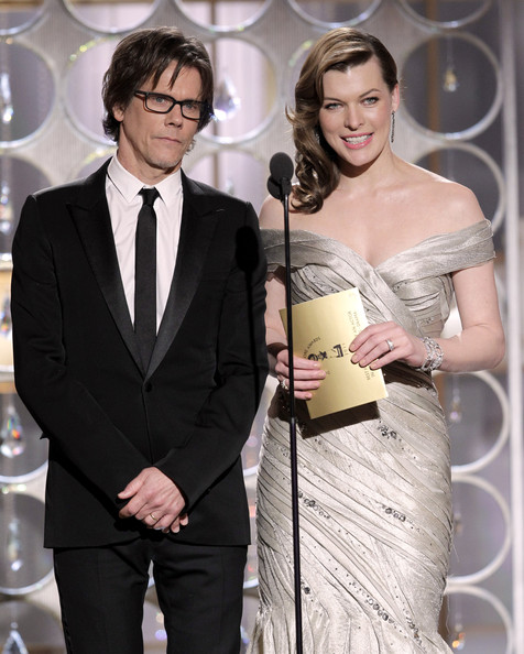 In this handout photo provided by NBC, Presenters Kevin Bacon and Milla Jovovich speak onstage during the Golden Globes at the Beverly Hilton International Ballroom on January 16, 2011 in Beverly Hills, California.