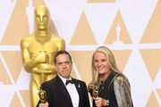 Filmmakers Lee Unkrich (L) and Darla K. Anderson, winners of the Best Animated Feature Film for 'Coco,' pose in the press room during the 90th Annual Academy Awards at Hollywood & Highland Center on March 4, 2018 in Hollywood, California.
