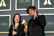 "Kwak Sin-ae (front) and Bong Joon-ho, winners of the Best Picture, Director, Original Screenplay, and International Feature Film awards for ""Parasite,"" pose in the press room during the 92nd Annual Academy Awards at Hollywood and Highland on February 09, 2020 in Hollywood, California."