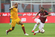 Gonzalo Higuain (R) of AC Milan competes for the ball with Steven Nzonzi (L) of AS Roma during the serie A match between AC Milan and AS Roma at Stadio Giuseppe Meazza on August 31, 2018 in Milan, Italy.