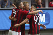 Keisuke Honda of AC Milan celebrates with his team-mates Jeremy Menez (L) and Stephan El Shaarawy (R) after scoring the opening goal during the Serie A match between AC Milan and SS Lazio at Stadio Giuseppe Meazza on August 31, 2014 in Milan, Italy.