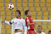 Javad Nekonam of Iran heads the ball ahead of Jong Tae Se of DPR Korea during the AFC Asian Cup Group D match between DPR Korea and Iran at Qatar Sports Club Stadium on January 15, 2011 in Doha, Qatar.