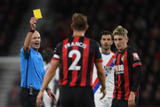 Refeeree Mike Dean gives a yellow card to David Brooks of Bournemouth (R) during the Premier League match between AFC Bournemouth and Crystal Palace at Vitality Stadium on October 1, 2018 in Bournemouth, United Kingdom.