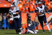 Tom Brady #12 of the New England Patriots is sacked by  Derek Wolfe #95 of the Denver Broncos in the first quarter in the AFC Championship game at Sports Authority Field at Mile High on January 24, 2016 in Denver, Colorado.