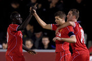 Steven Gerrard of Liverpool is congratulated by teammates Mamadou Sakho (L) and Jordan Henderson (R) after scoring his team's second goal from a free kick during the FA Cup Third Round match between AFC Wimbledon and Liverpool at The Cherry Red Records Stadium on January 5, 2015 in Kingston upon Thames, England.