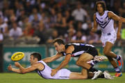 Hayden Ballantyne of the Dockers handpasses the ball away from Steele Sidebottom of the Magpies during the round one AFL match between the Collingwood Magpies and the Fremantle Dockers at Etihad Stadium on March 14, 2014 in Melbourne, Australia.