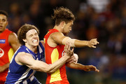 Ben Brown of the Kangaroos tackles Jarrod Harbrow of the Suns during the round 16 AFL match between the North Melbourne Kangaroos and the Gold Coast Titans at Etihad Stadium on July 8, 2018 in Melbourne, Australia.