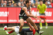 Steele Sidebottom of the Magpies handballs whilst being tackled by Angus Brayshaw of the Demons during the round 18 AFL match between the Collingwood Magpies and the Melbourne Demons at Melbourne Cricket Ground on August 1, 2015 in Melbourne, Australia.