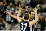 Steele Sidebottom and Kyle Martin of the Magpies celebrate a goal   during the round 19 AFL match between the Collingwood Magpies and the Port Adelaide Power at Melbourne Cricket Ground on August 3, 2014 in Melbourne, Australia.