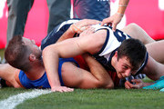 Jack Henry of the Cats and Josh Walker of the Lions recover after colliding with the goalpost in a marking contest during the 2018 AFL round 19 match between the Geelong Cats and the Brisbane Lions at GMHBA Stadium on July 28, 2018 in Geelong, Australia.