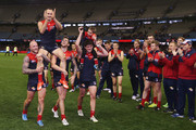 Daniel Cross of the Demons gets carried off by Nathan Jones (L) and Jeremy Howe with his son Tyler being carried off by Angus Brayshaw during the round 23 AFL match between the Melbourne Demons and the Greater Western Sydney Giants at Etihad Stadium on September 6, 2015 in Melbourne, Australia.