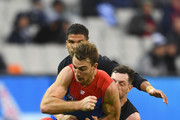 Tim Smith of the Demons handballs whilst being tackled by Darcy Lang of the Blues during the round nine AFL match between the Carlton Blues and the Melbourne Demons at Melbourne Cricket Ground on May 20, 2018 in Melbourne, Australia.