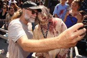 Greg Nicotero takes a photo with a fan at The Walking Dead Walker Horde at Petco Park during Comic Con 2019 on July 20, 2019 in San Diego, California.